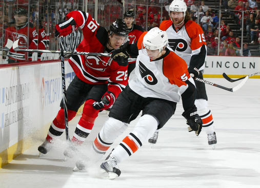 NEWARK, NJ - APRIL 14: Braydon Coburn #5 of the Philadelphia Flyers and Patrik Elias #26 of the New Jersey Devils battle for a loose puck in Game One of the Eastern Conference Quarterfinals during the 2010 NHL Stanley Cup Playoffs at the Prudential Center on April 14, 2010 in Newark, New Jersey. (Photo by Andy Marlin/NHLI via Getty Images)