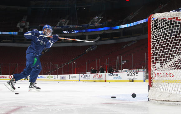 VANCOUVER, CANADA - MAY 15: Manny Malhotra #27 of the Vancouver Canucks shoots the puck into the net during the game day skate before Game One of the Western Conference Finals against the San Jose Sharks during the 2011 NHL Stanley Cup Playoffs at Rogers Arena on May 15, 2011 in Vancouver, British Columbia, Canada. (Photo by Jeff Vinnick/NHLI via Getty Images)