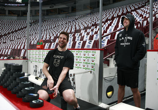 VANCOUVER, CANADA - APRIL 13:  Willie Mitchell #33 and Anze Kopitar #11 of the Los Angeles Kings share a laugh as they stand on their bench before Game Two of the Western Conference Quarterfinals of the 2012 NHL Stanley Cup Finals against the Vancouver Canucks at Rogers Arena on April 13, 2012 in Vancouver, British Columbia, Canada.  (Photo by Jeff Vinnick/NHLI via Getty Images)
