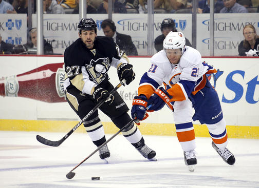 PITTSBURGH, PA - MAY 09: Kyle Okposo #21 of the New York Islanders handles the puck in front of Craig Adams #27 of the Pittsburgh Penguins in Game Five of the Eastern Conference Quarterfinals during the 2013 NHL Stanley Cup Playoffs at Consol Energy Center on May 9, 2013 in Pittsburgh, Pennsylvania. (Photo by Justin K. Aller/Getty Images)