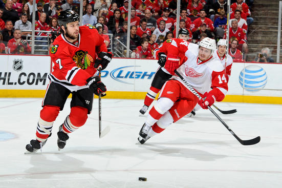 CHICAGO, IL - MAY 18: Brent Seabrook #7 of the Chicago Blackhawks passes the puck up the ice as Gustav Nyquist #14 of the Detroit Red Wings watches, in Game Two of the Western Conference Semifinals during the 2013 Stanley Cup Playoffs at the United Center on May 18, 2013 in Chicago, Illinois. (Photo by Bill Smith/NHLI via Getty Images)