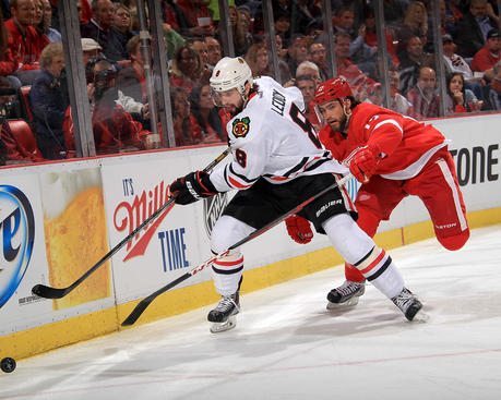 DETROIT, MI - MAY 23:  Nick Leddy #8 of the Chicago Blackhawks goes into the corner for the puck as Patrick Eaves #17 of the Detroit Red Wings pressures him during Game Four of the Western Conference Semifinals during the 2013 NHL Stanley Cup Playoffs at Joe Louis Arena on May 23, 2013 in Detroit, Michigan.  (Photo by Dave Reginek/NHLI via Getty Images)