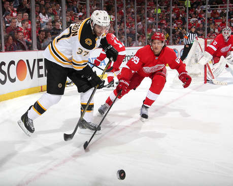 DETROIT, MI - APRIL 24:  Patrice Bergeron #37 of the Boston Bruins and Danny DeKeyser #65 of the Detroit Red Wings battle for the puck during Game Four of the First Round of the 2014 Stanley Cup Playoffs on April 24, 2014 at Joe Louis Arena in Detroit, Michigan. (Photo by Dave Reginek/NHLI via Getty Images)