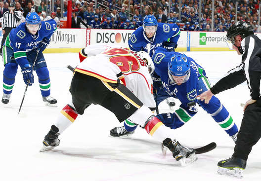 VANCOUVER, BC - APRIL 15:  Henrik Sedin #33 of the Vancouver Canucks and Josh Jooris #86 of the Calgary Flames take a face-off during Game One of the Western Conference Quarterfinals of the 2015 NHL Stanley Cup Playoffs at Rogers Arena on April 15, 2015 in Vancouver, British Columbia, Canada.  (Photo by Jeff Vinnick/NHLI via Getty Images)