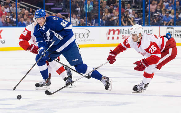 TAMPA, FL - APRIL 16: Andrej Sustr #62 of the Tampa Bay Lightning carries the puck against Tomas Jurco #26 of the Detroit Red Wings during the first period in Game One of the Eastern Conference Quarterfinals during the 2015 NHL Stanley Cup Playoffs at the Amalie Arena on April 16, 2015 in Tampa, Florida.  (Photo by Scott Audette/NHLI via Getty Images)