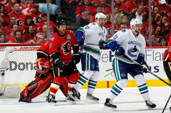 CALGARY, AB - APRIL 19: Dennis Wideman #6 of the Calgary Flames skates against Daniel Sedin #22 and Alex Edler #23 of the Vancouver Canucks at Scotiabank Saddledome for Game Three of the Western Quarterfinals during the 2015 NHL Stanley Cup Playoffs on April 19, 2015 in Calgary, Alberta, Canada. (Photo by Gerry Thomas/NHLI via Getty Images)
