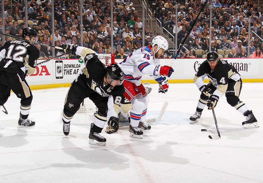 PITTSBURGH, PA - APRIL 20:  Rob Scuderi #4 moves the puck in front of Tanner Glass #15 of the New York Rangers and Sidney Crosby #87 of the Pittsburgh Penguins in Game Three of the Eastern Conference Quarterfinals during the 2015 Stanley Cup Playoffs at Consol Energy Center on April 20, 2015 in Pittsburgh, Pennsylvania.  (Photo by Gregory Shamus/NHLI via Getty Images)