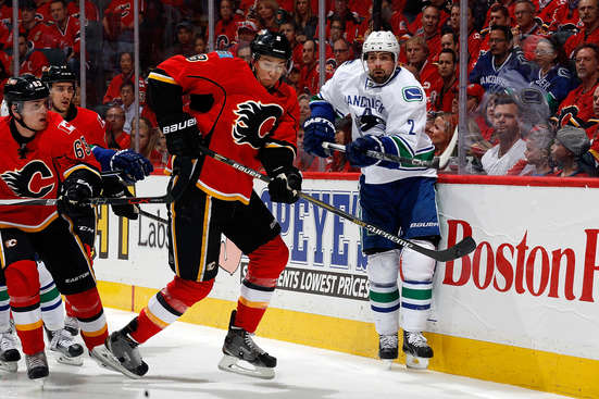 CALGARY, AB - APRIL 21: Joe Colborne #8 of the Calgary Flames skates against Dan Hamhuis #2 of the Vancouver Canucks at Scotiabank Saddledome for Game Four of the Western Quarterfinals during the 2015 NHL Stanley Cup Playoffs on April 21, 2015 in Calgary, Alberta, Canada. (Photo by Gerry Thomas/NHLI via Getty Images)