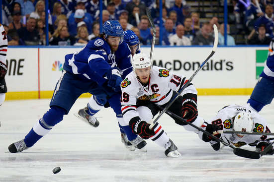 TAMPA, FL - JUNE 06:  Jonathan Toews #19 of the Chicago Blackhawks falls to ice against Victor Hedman #77 of the Tampa Bay Lightning during the first period in Game Two of the 2015 NHL Stanley Cup Final at Amalie Arena on June 6, 2015 in Tampa, Florida.  (Photo by Bruce Bennett/Getty Images)